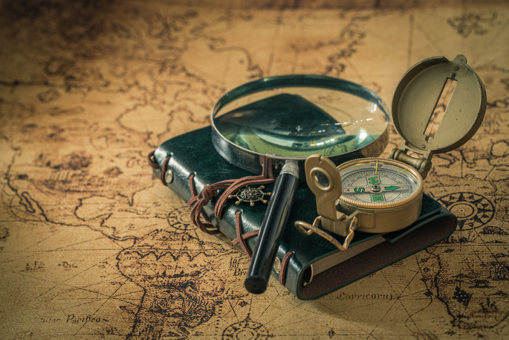 old map with compass, notebook and magnifying glass. The concept